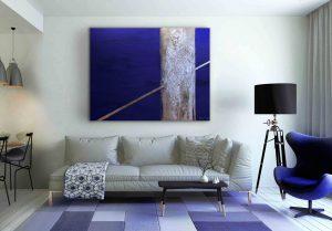 """Blaues Bild """"Seilgänger"""" im weiß-blauen Wohnzimmer über die Couch."""